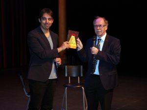 George van Hal overhandigt het eerste exemplaar van zijn boek Robots, aliens & popcorn aan Nobelprijswinnaar Gerard 't Hooft.