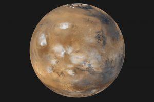 Op de droge planeet zijn enkele wolken gespot door de Mars Global Surveyor. Foto: NASA/JPL/MSSS