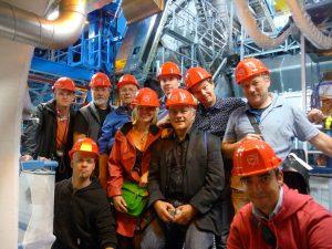 Een gedeelte van de deelnemers staan samen met reisleider Dafne (in het midden) en New Scientist-redacteur George van Hal (rechts) voor de ATLAS-detector