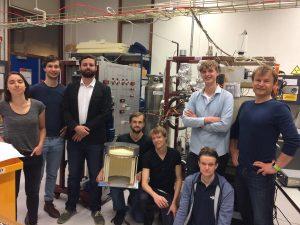 Nikhef-onderzoekers in hun lab op Amsterdam Science Park. Op de achtergrond de opstelling voor het toekomstige XenonNT-experiment. Het model in het midden (schaal 1:1) was het voorgaande kleinere Xenon100-experiment.