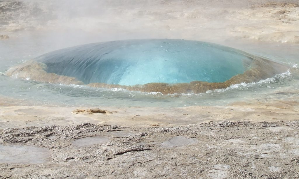 IJsland is vulkanisch nog altijd bijzonder actief. Dat zie je hier in Strokkur, waar een actieve geiser op het punt van uitbarsten staat. Door de bolvorm van het wateroppervlak - iets dat slechts een fractie van een seconde zo is - ontstaat lenswerking, met een bonte kleurenpracht tot gevolg.