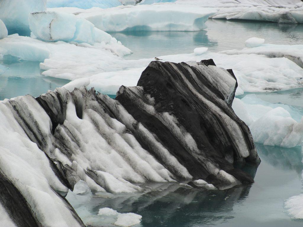 Kleurrijke ijsrotsen dobberen rond in een gletsjermeer, een schouwspel dat je in IJsland op een aantal plekken kunt aanschouwen.